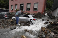 A man looks at a car that is covered in Hagen, Germany, Wednesday, July 15, 2021 with the debris brought by the flooding of the 'Nahma' river the night before. The heavy rainfalls had turned the small river into a raging torrent. (Roberto Pfeil/dpa via AP)