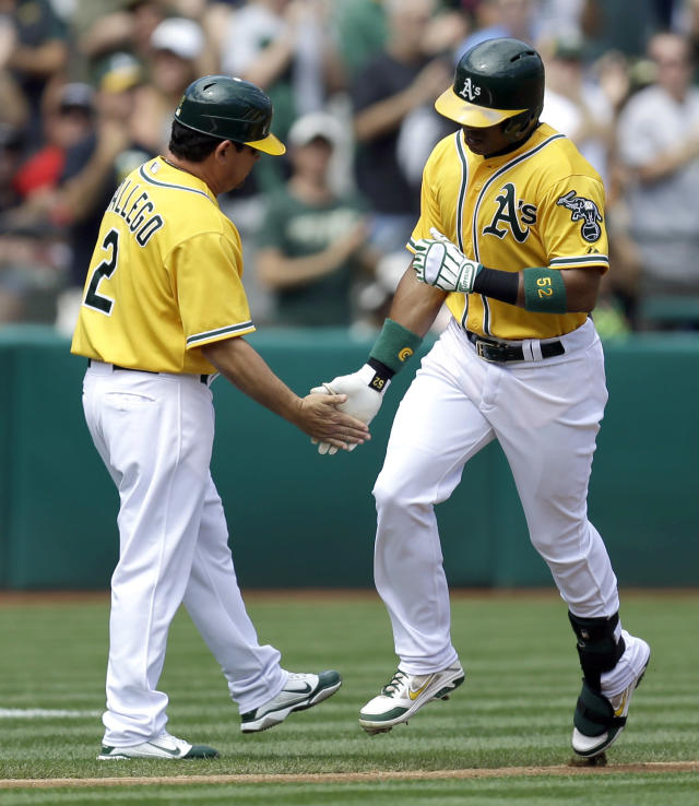 Oakland Athletics' Yoenis Cespedes, right, is congratulated by third base coach Mike Gallego (2) after Cespedes hit a home run off Texas Rangers' Derek Holland in the second inning of a baseball game, Monday, Sept. 2, 2013, in Oakland, Calif. (AP Photo/Ben Margot)