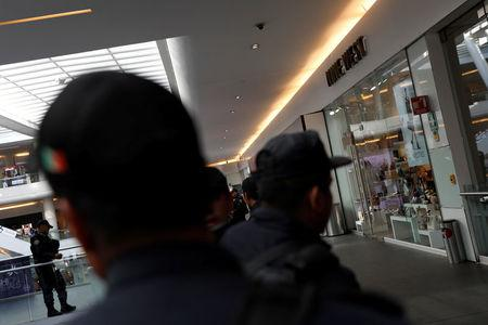 Police work outside a footwear shop after a man shot a woman in the abdomen there before shooting himself in the head according to a police statement in Mexico City, Mexico March 19, 2018. REUTERS/Carlos Jasso