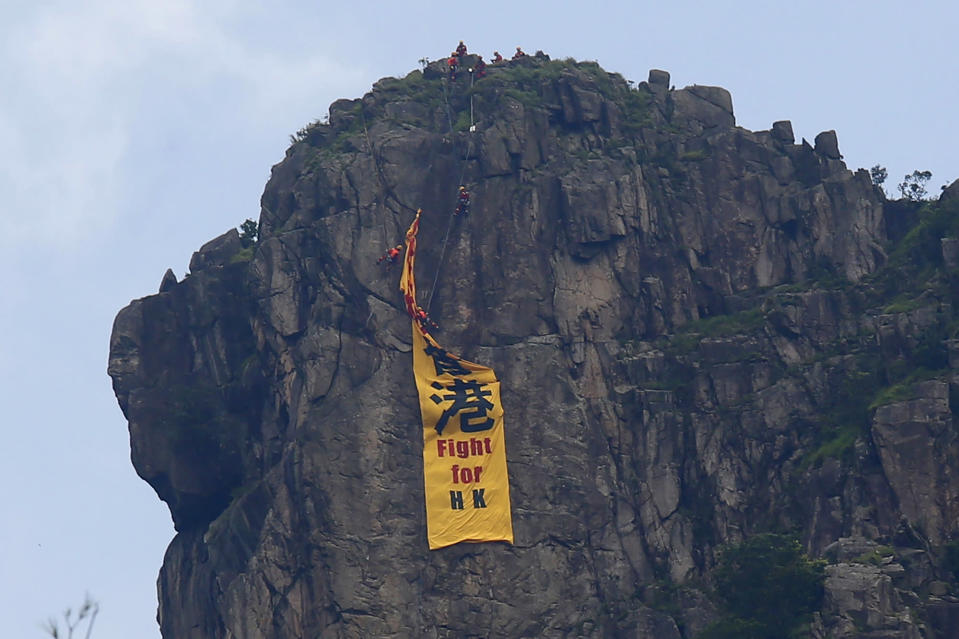 """Firefighters remove a yellow banner with the words """"Fight for Hong Kong"""" in Chinese and English which is hung on the Lion Rock mountain by pro-democracy protesters in Hong Kong, Sunday, June 16, 2019. Hong Kong was bracing Sunday for another massive protest over an unpopular extradition bill that has highlighted the territory's apprehension about relations with mainland China, a week after the crisis brought as many as 1 million into the streets. (AP Photo/Kin Cheung)"""