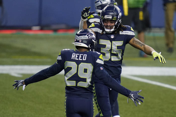 Seattle Seahawks strong safety Ryan Neal (35) and Seattle Seahawks free safety D.J. Reed (29) celebrate a play during the second half of an NFL football game against the Los Angeles Rams, Sunday, Dec. 27, 2020, in Seattle. The Seahawks won 20-9. (AP Photo/Elaine Thompson)