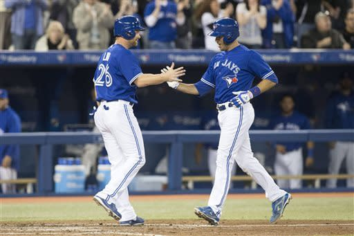 Toronto Blue Jays' J.P. Arencibia, right, is greetted at home plate by Adam Lind after hitting a two-run home run against the Boston Red Sox during the fourth inning of a baseball game in Toronto on Saturday, April 6, 2013.(AP Photo/The Canadian Press, Chris Young)