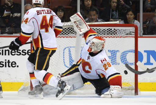 Calgary Flames goalie Reto Berra, right, of Switzerland, is scored on by Anaheim Ducks left wing Dustin Penner as defenseman Chris Butler looks on during the third period of an NHL hockey game, Friday, Nov. 29, 2013, in Anaheim, Calif. (AP Photo/Mark J. Terrill)
