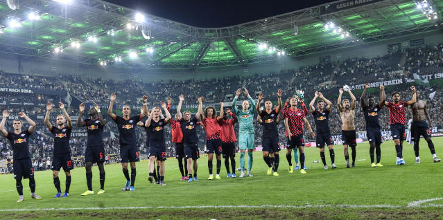 Leipzig's team celebrates after winning the German Bundesliga soccer match between Borussia Moenchengladbach and RB Leipzig in Moenchengladbach, Germany, Friday, Aug. 30, 2019. (AP Photo/Martin Meissner)