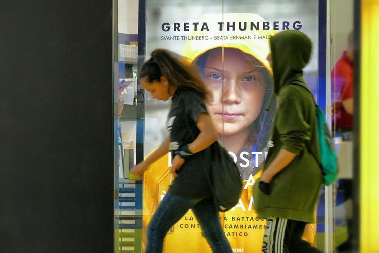 Young people walk past a sign advertising Greta Thunberg's book in Italy.