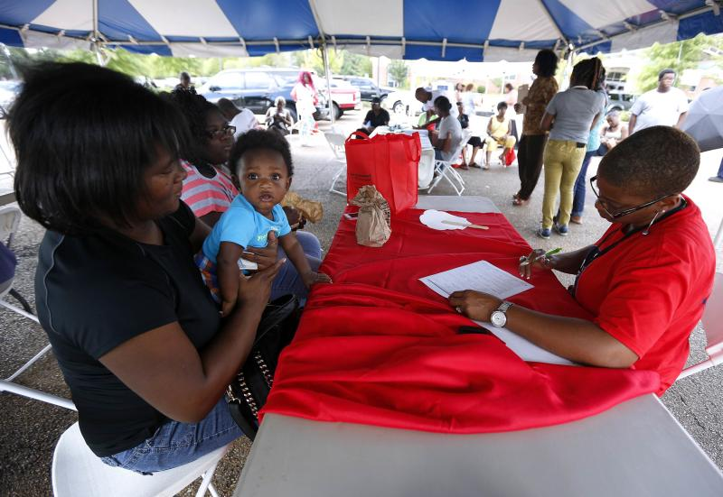 """Lisa Smith (R) helps uninsured Danielle Winters (L) and her 7-month-old grandson Tyler, who is on medicare, sign up for the Affordable Care Act, or """"Obamacare"""", outside the Jackson-Hinds Comprehensive Health Center in Jackson, Mississippi October 4, 2013. Mississippi is one of at least 20 states that has decided not to expand Medicaid under the Affordable Care Act. REUTERS/Jonathan Bachman (UNITED STATES)"""