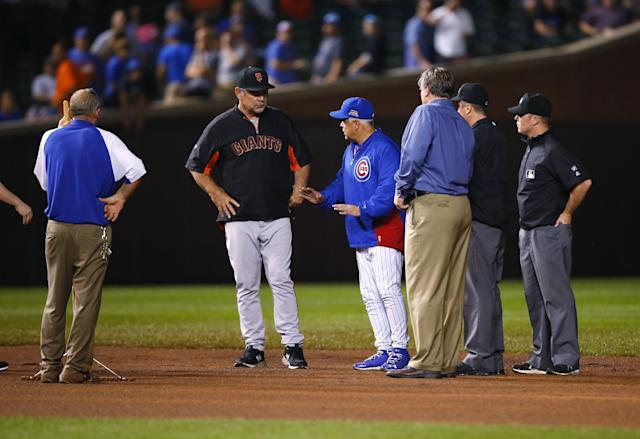 Chicago Cubs manager Rick Renteria, center right, and San Francisco Giants manager Bruce Bochy talk with the umpires and officials on the field after a heavy rain soaked Wrigley Field during the fifth inning of a baseball game between the San Francisco Giants and the Chicago Cubs on Tuesday, Aug. 19, 2014, in Chicago. (AP Photo/Jeff Haynes)