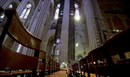 FILE PHOTO:    A man sits in the pews of Cathedral of St. John the Divine in New York, June 25, 2013.   REUTERS/Carlo Allegri/File Photo