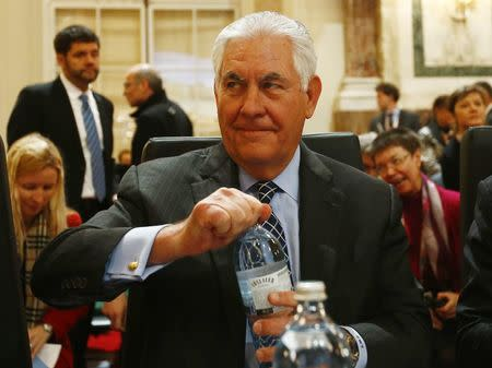 U.S. Secretary of State Tillerson opens a bottle of water at the beginning of a meeting of OSCE Foreign Ministers in Vienna