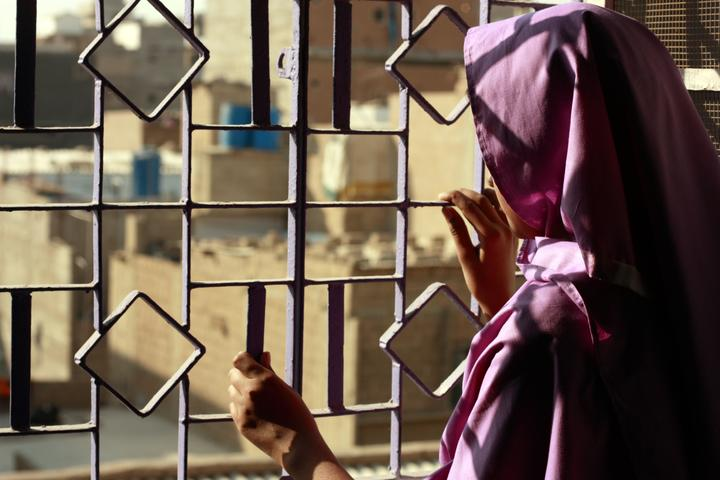Photo shows a woman looking out a window with bars