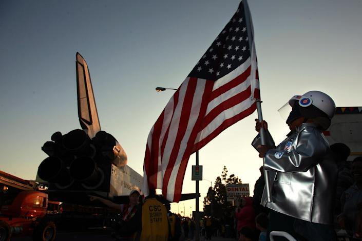 "Amir Morris, 3, wear an astronaut costume while holding an American flag, as the space shuttle Endeavor passes Manchester Blvd in Inglewood, Calif., Saturday, Oct. 13, 2012. The Endeavour's terrestrial journey began before dawn Friday when it departed from the Los Angeles International Airport, rolling on a 160-wheeled carrier past diamond-shaped ""Shuttle Xing"" signs. Over two days, it will trundle 12 miles (19 kilometers) at a top speed of 2 mph (3 kph) to its final destination, the California Science Center where it will be the centerpiece of a new exhibit. (AP Photo/Los Angeles Times, Rick Loomis, Pool)"