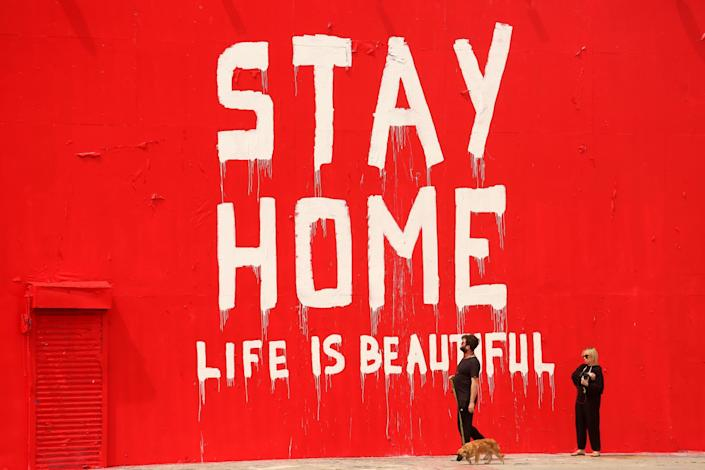 "A message painted on a wall on La Brea Avenue on March 31 reads: ""Stay home. Life is beautiful."""