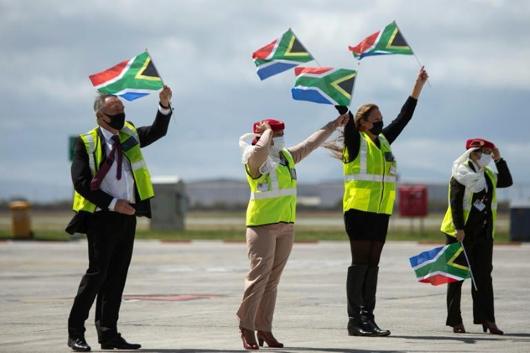 Ground crew wave flags as an Emirates airliner lands in Cape Town from Dubai, marking the end of South Africa's long ban on international flights