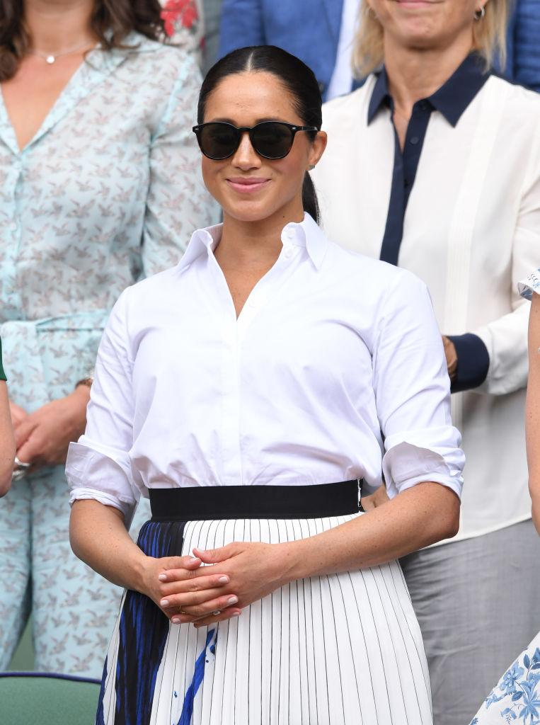 Meghan chose a Givenchy white shirt and pleated skirt by Hugo Boss for the Wimbledon outing. She completed the look with a Stella McCartney bag. [Photo: Getty]