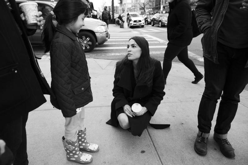 Ocasio-Cortez talks with a staff member's daughter near the office in Jackson Heights.