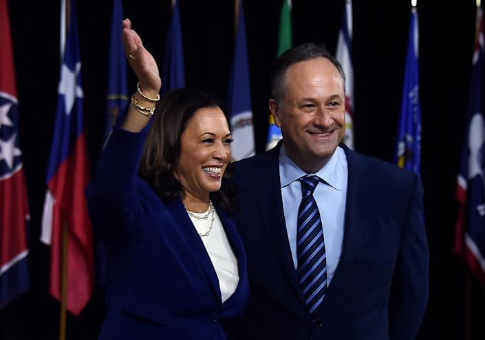 Democratic vice presidential running mate Kamala Harris and her husband Douglas Emhoff pose on stage after the first Biden-Harris press conference in Wilmington, Delaware, on August 12, 2020.