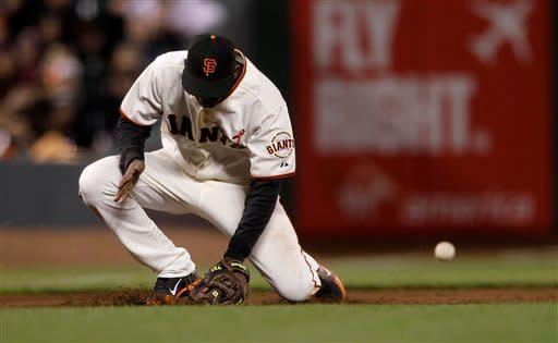 San Francisco Giants third baseman Joaquin Arias makes an error on a ground ball hit by Colorado Rockies' Marco Scutaro that scored Jonathan Herrera during the ninth inning of a baseball game in San Francisco, Monday, May 14, 2012. The Giants won 3-2. (AP Photo/Jeff Chiu)