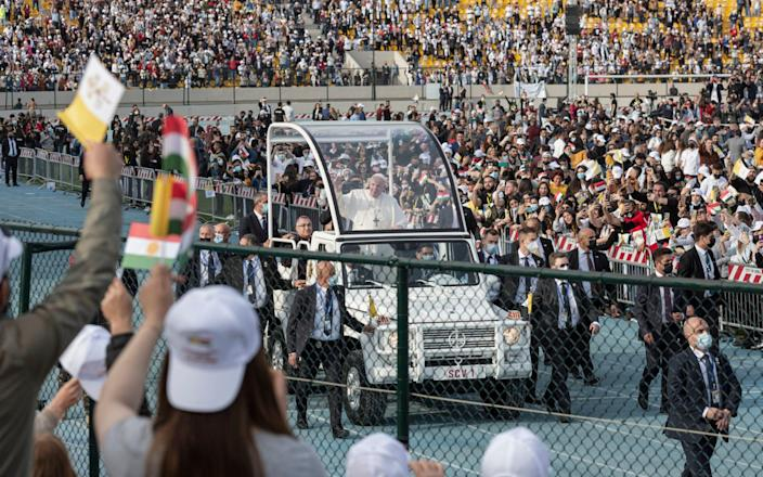 Crowds of some 10,000 people watch Pope Francis arrive at a stadium in Erbil, Iraq - am Tarling for The Telegraph