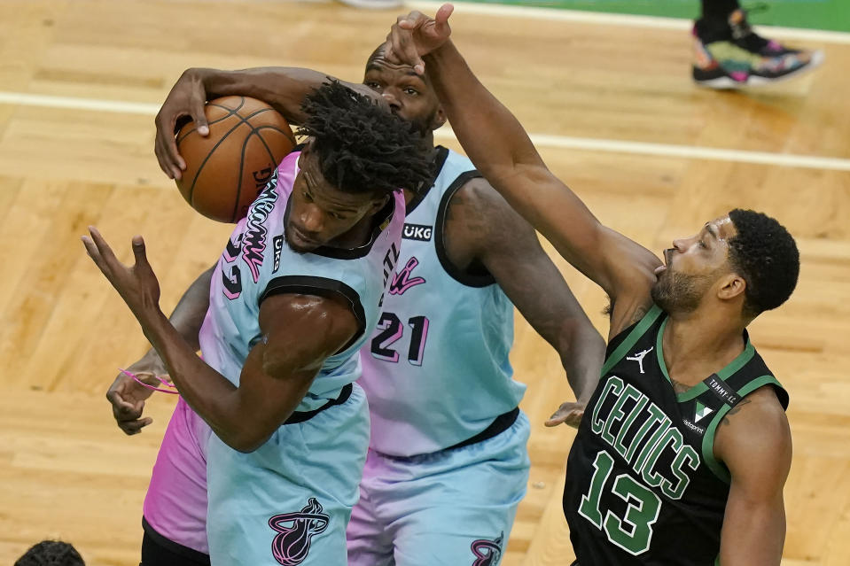 Miami Heat's Jimmy Butler, left, grabs a rebound as Boston Celtics' Tristan Thompson, right, vies for the ball while Heat's Dewayne Dedmon, behind, looks on in the first half of a basketball game, Sunday, May 9, 2021, in Boston. (AP Photo/Steven Senne)