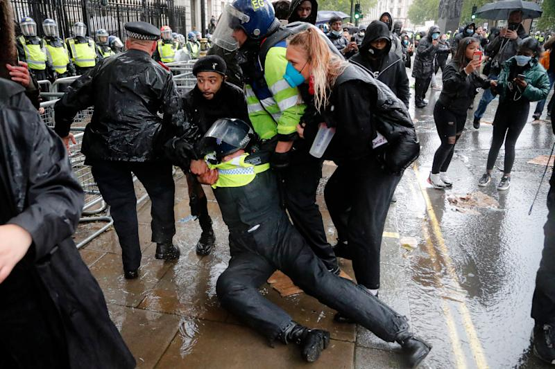 A police officer was injured when falling of a horse during scuffles with demonstrators at Downing Street. (Photo: ASSOCIATED PRESS)