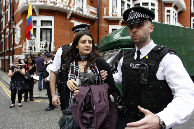 British police officers move a protester in support of WikiLeaks founder Julian Assange from the front of Ecuadorian Embassy in central London, London, Thursday, Aug. 16, 2012. WikiLeaks founder Julian Assange entered the embassy in June in an attempt to gain political asylum to prevent him from being extradited to Sweden, where he faces allegations of sex crimes, which he denies. (AP Photo/Sang Tan)