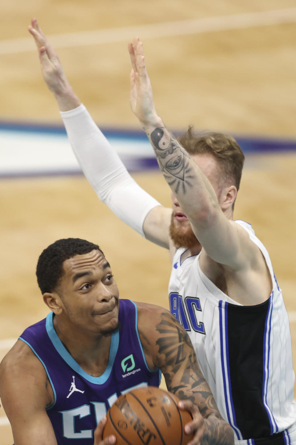 Charlotte Hornets forward P.J. Washington, left, is defended by Orlando Magic forward Ignas Brazdeikis during the first half of an NBA basketball game in Charlotte, N.C., Friday, May 7, 2021. (AP Photo/Nell Redmond)