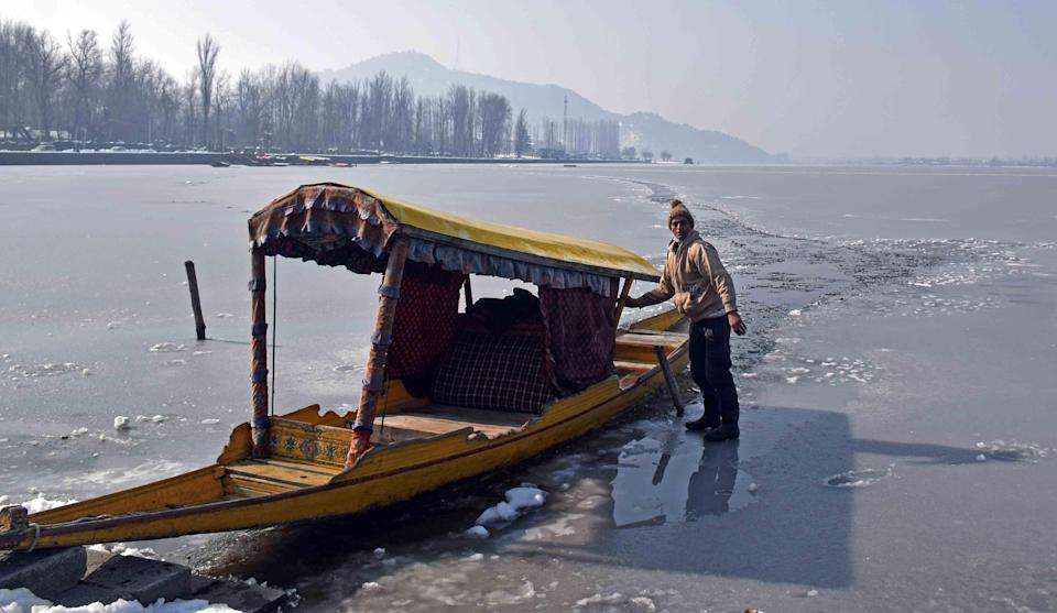 A man poses for a photograph on the frozen Dal Lake.