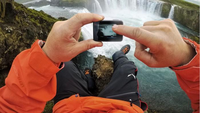 Man pressing touchscreen to take photo of a waterfall using GoPro camera.