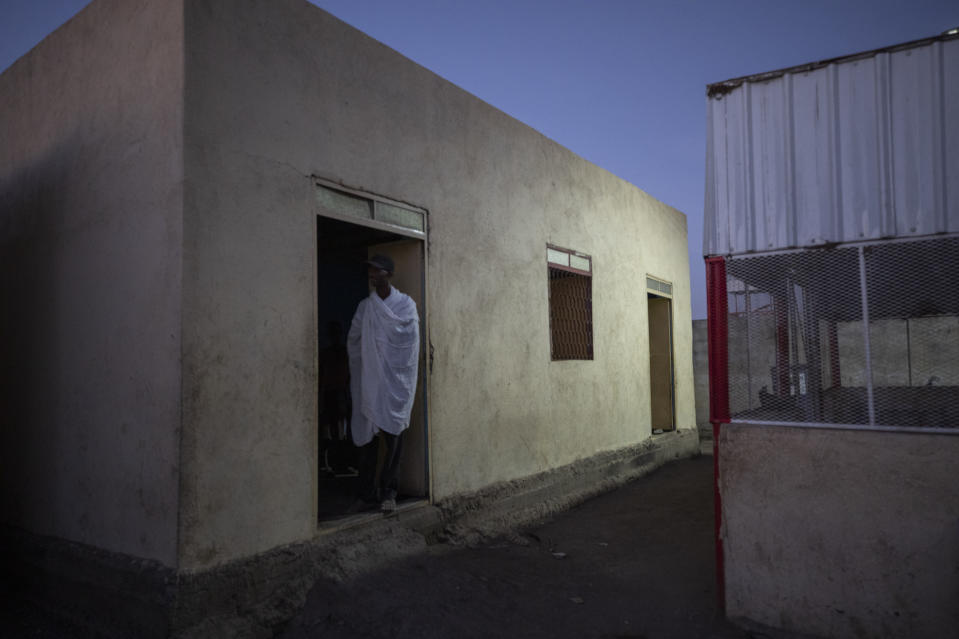 Tigrayan refugee Abraha Kinfe Gebremariam, 40, stands in a doorway of his family's shelter early morning in Hamdayet, eastern Sudan, near the border with Ethiopia, on March 21, 2021. His village of Mai Kadra was the first known massacre of a conflict in which thousands of ethnic Tigrayans like his family have been killed. (AP Photo/Nariman El-Mofty)
