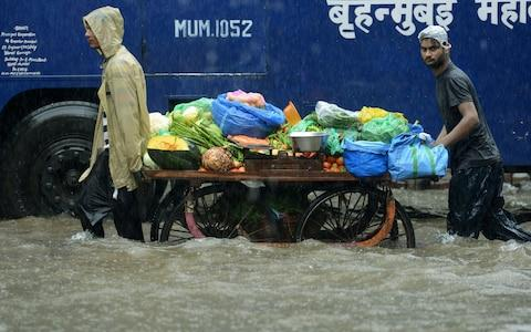 Indian vegetable vendors push their cart along a flooded street during heavy rain showers in Mumbai - Credit: Punit Paranjpe/AFP