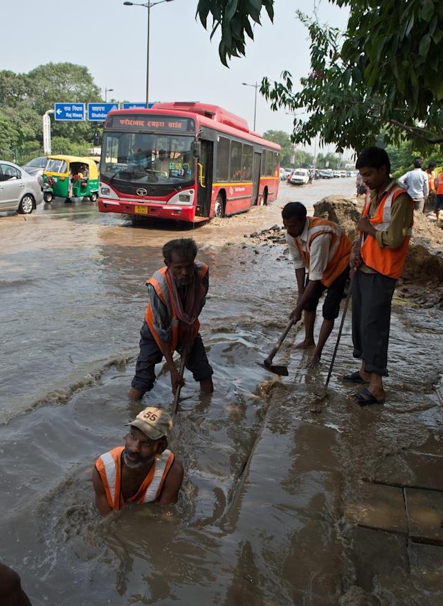 Indian workers from the Municipal Corporation of Delhi (MCD) clear a clogged drain on a water logged road as the waters of the Yamuna River rise in New Delhi on June 20, 2013. Military helicopters dropped emergency supplies June 19 to thousands of people stranded by flash floods that tore through towns and temples in northern India and neighbouring Nepal, killing more than 160, officials said. AFP PHOTO/ Prakash SINGH