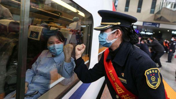 PHOTO: This photo taken on Feb. 13, 2020 in Nanchang, China, shows a train attendant gesturing to medical staff leaving for Wuhan, the epicenter of a novel coronavirus outbreak. (Str/AFP via Getty Images)