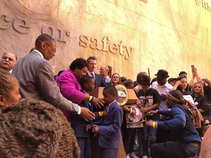 """Gov. Gavin Newsom, behind lectern, is joined by Assemblywoman Shirley Weber (D-San Diego) and families who have lost loved ones to police violence for a bill-signing ceremony for AB 392, a reform of California's use of force rules for law enforcement, in Aug. 2019. <span class=""""copyright"""">(Anita Chabria / Los Angeles Times)</span>"""