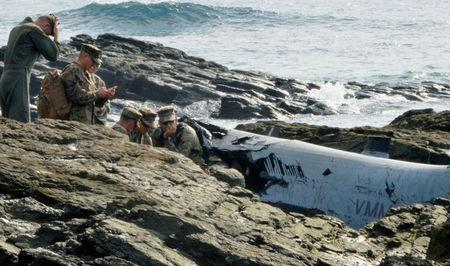 U.S. military personnel investigate the wreckage of a U.S. Marine Corps MV-22 Osprey aircraft that crash-landed in the sea off Nago