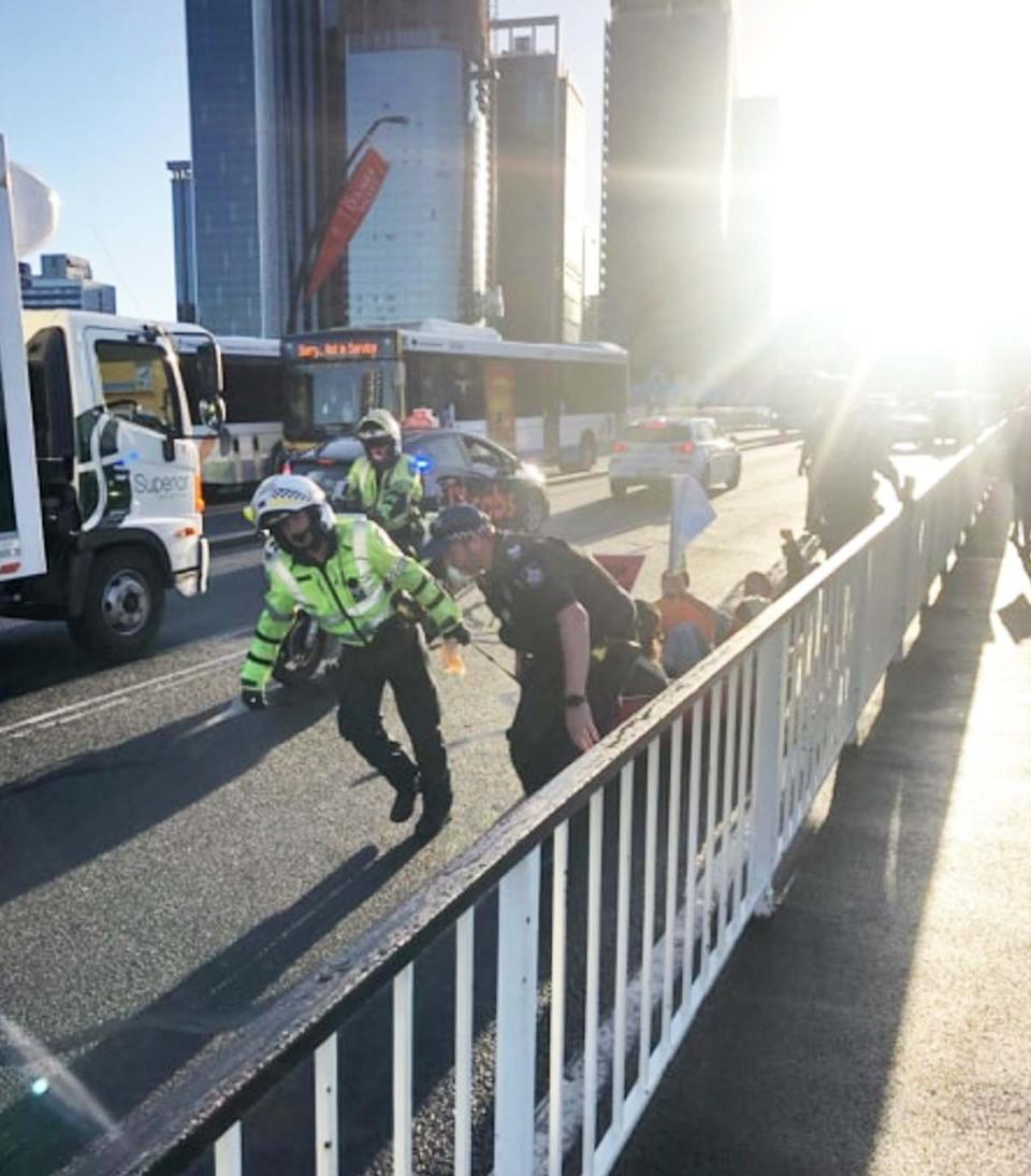 Emergency response personnel drag the canoe from Victoria Bridge in Brisbane.