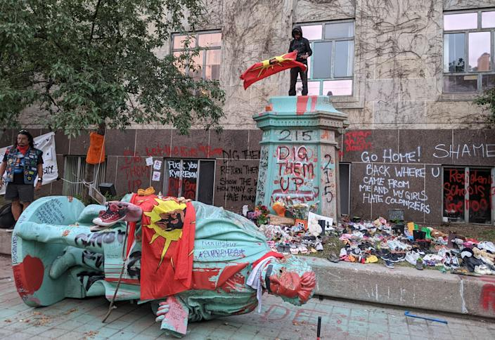 <p>A man waving the Mohawk Warrior Society flag stands on the pedestal of the toppled statue of Egerton Ryerson, one of the architects of indigenous boarding school system, in Toronto on June 6, 2021. </p> (AFP via Getty Images)