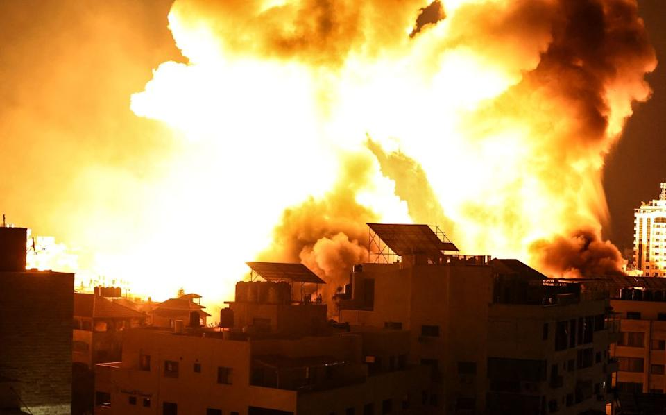 A ball of fire explodes above buildings in Gaza City as Israeli forces shell the Palestinian enclave.