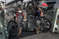 Men wearing protective masks carry their bicycles at an overpass in Quezon city, Philippines, Saturday, Sept. 26, 2020. Public transportation remains limited and the government orders commuters to wear face shields and face masks to help curb the spread of the coronavirus. (AP Photo/Aaron Favila)
