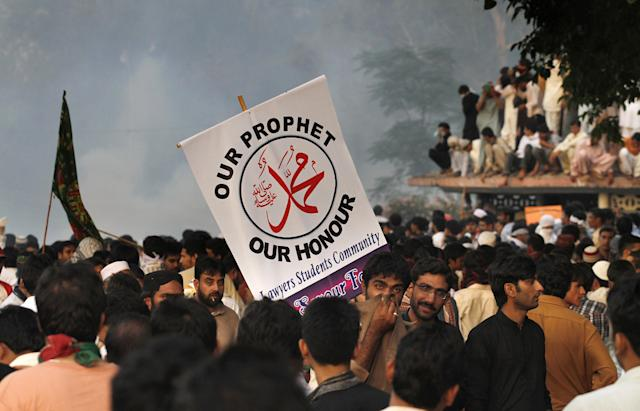 Pakistani protestors gather as police fire tear gas to disperse them during clashes that erupted as protestors tried to approach the U.S. embassy, Friday, Sept. 21, 2012 in Islamabad, Pakistan. Protests by tens of thousands of Pakistanis infuriated by an anti-Islam film descended into deadly violence on Friday, with police firing tear gas and live ammunition in an attempt to subdue rioters who hurled rocks and set fire to buildings in some cities. Four people were killed and dozens injured on a holiday declared by Pakistan's government so people could rally against the video. (AP Photo/Anjum Naveed)