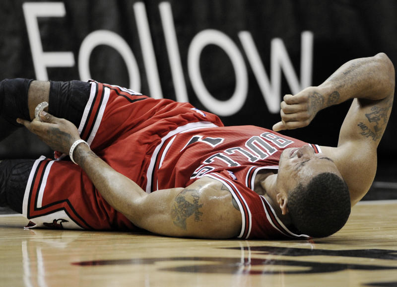 Chicago Bulls' Derrick Rose reacts after injuring his leg during the first half of an NBA basketball game against the San Antonio Spurs, Wednesday, Feb. 29, 2012, in San Antonio. (AP Photo/Darren Abate)