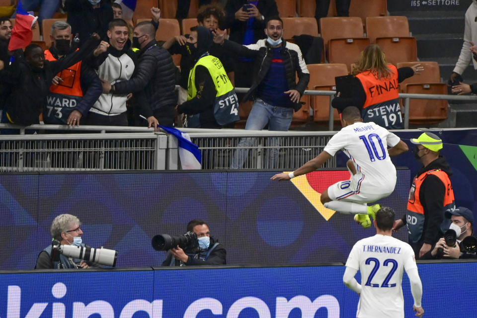 France's Kylian Mbappe leaps the fence as he celebrates after scoring his team's second goal during the UEFA Nations League final soccer match between Spain and France at the San Siro stadium, in Milan, Italy, Sunday, Oct. 10, 2021. (Miguel Medina/Pool Photo via AP)