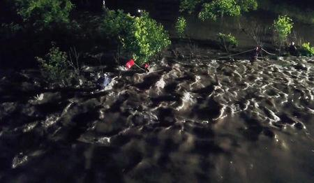 Rescue services help a man whose vehicle had been swept off the roadway by fast-moving water in Broken Arrow, Oklahoma, U.S., May 21, 2019 in this picture obtained from social media on May 21, 2019. Broken Arrow Fire Department/via REUTERS