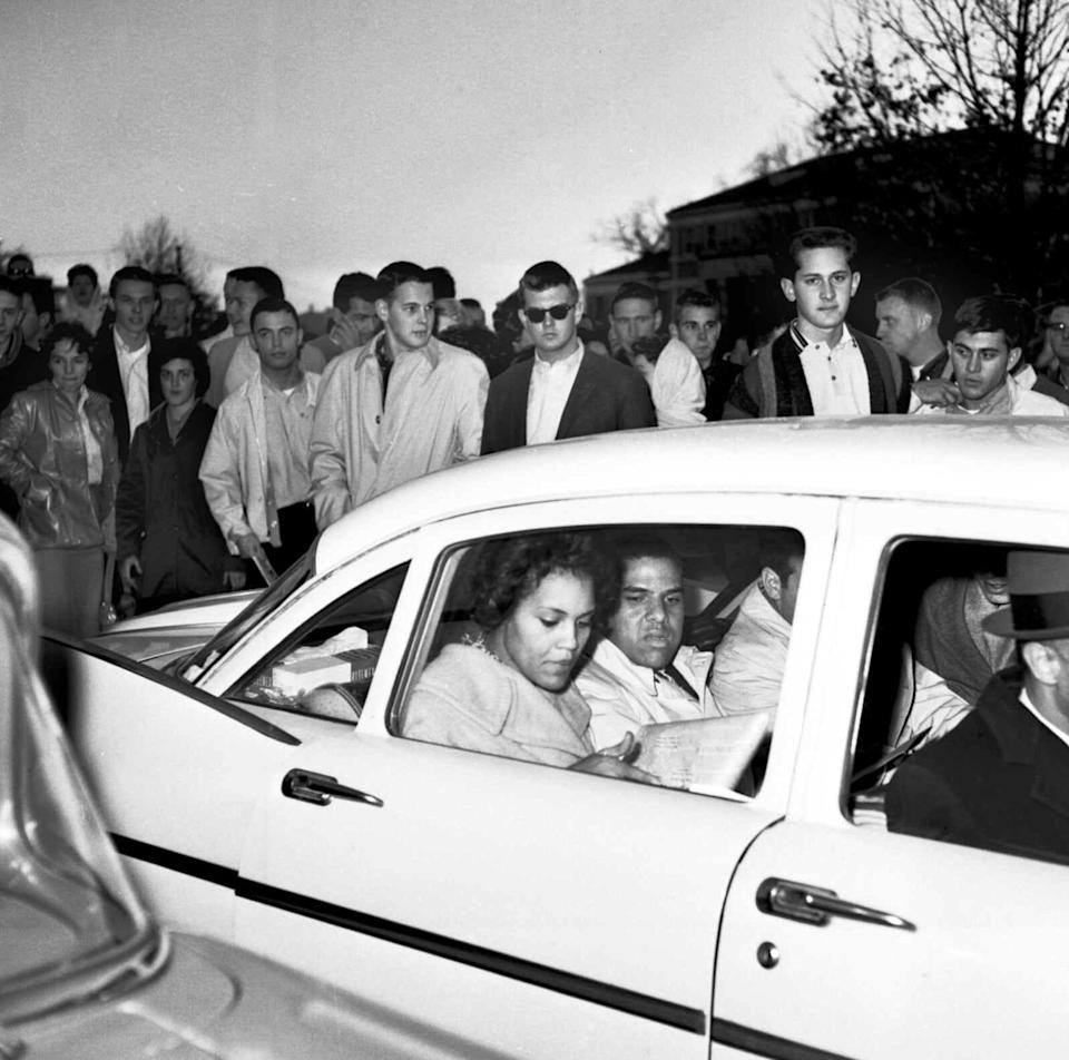 University of Georgia students shout and jeer in this 1961 photo at Charlayne Hunter, 18, left, and Hamilton Holmes, 19, as they leave the administration building after completing registration at Athens, Ga.