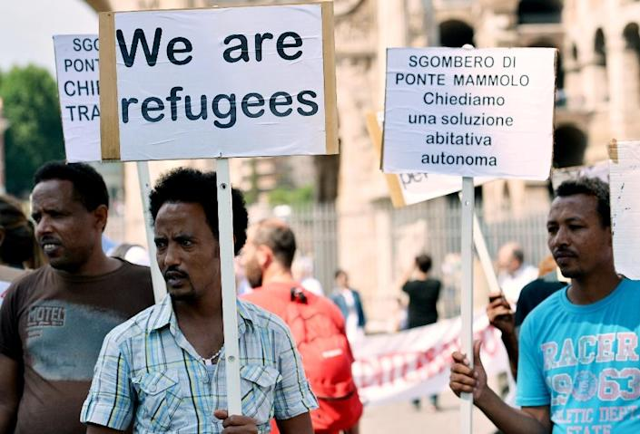 """A participant holds a sign reading """"We are refugees"""" during a demonstration in downtown Rome to mark World Refugee Day on June 20, 2015 (AFP Photo/Tiziana Fabi)"""