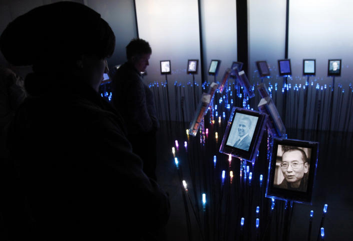 FILE - In this Thursday Dec. 9, 2010 file photo, visitors to the Nobel Garden in the Nobel Peace Center look at a picture of Nobel peace laureate Liu Xiaobo, right, in Oslo, Norway. Mainly associated with conflict resolution, foreign assistance and cozy Scandinavian prosperity, Norway makes an odd target for China's ire. Yet for three years, Beijing has frozen relations with Oslo since a committee appointed by the Norwegian parliament awarded the 2010 Nobel Peace Prize to imprisoned Chinese dissident Liu Xiaobo, deeply embarrassing China's leaders. Diplomatic ties have been gutted, meetings canceled and economic ties hamstrung by unofficial embargoes on Norwegian salmon and trade talks. (AP Photo/John McConnico, File)