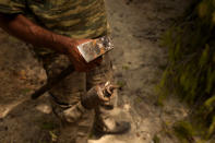 Christos Livas, 48, resin collector holds his tools at a pine forest near Agdines village on the island of Evia, about 185 kilometers (115 miles) north of Athens, Greece, Wednesday, Aug. 11, 2021. Residents in the north of the Greek island of Evia have made their living from the dense pine forests surrounding their villages for generations. Tapping the pine trees for their resin has been a key source of income for hundreds of families. But hardly any forests are left after one of Greece's most destructive single wildfires in decades rampaged across northern Evia for days. (AP Photo/Petros Karadjias)