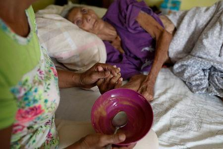 Judith Palmar holds her mother Sibilina Caro hand after feeding her at their home in Maracaibo, Venezuela July 25, 2018. Picture taken July 25, 2018. REUTERS/Marco Bello