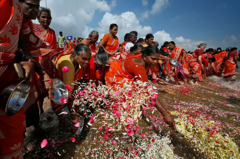 Women scatter flower petals in the waters of the Bay of Bengal during a prayer ceremony for the victims of the 2004 tsunami on the 15th anniversary of the disaster, in Chennai