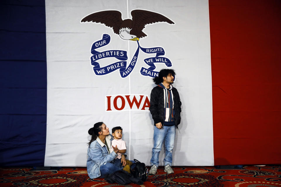 Natalie Serrano, left, and Isaac Garcia watch caucus returns come in with their son Leonel, 2, at a Democratic presidential candidate Sen. Bernie Sanders, I-Vt., caucus night campaign rally in Des Moines, Iowa, Monday, Feb. 3, 2020. (AP Photo/Matt Rourke)