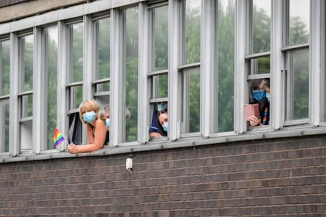 People wear masks as they watch the Prince of Wales and the Duchess of Cornwall through the hospital windows. (PA Images)
